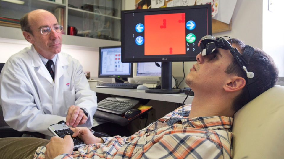 Professor Robert Hess, left, director of research at the department of ophthalmology at McGill University and Dr. Simon Clavagnier, a McGill vision research associate, demonstrate the effect of wearing goggles while playing the game Tetris in Montreal, Monday, April 22, 2013. (Graham Hughes / THE CANADIAN PRESS)