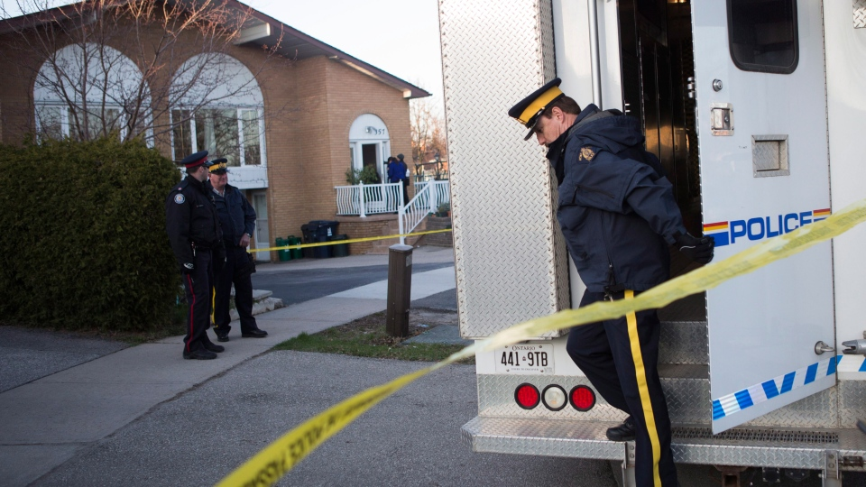 RCMP officers stand outside the Toronto home of one of the two men accused of plotting a terror attack on a rail target on Monday, April 22, 2013. (Chris Young / THE CANADIAN PRESS)