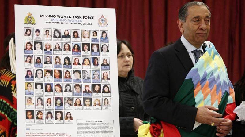 Commissioner Wally Oppal, right, stands next to a display with photographs of missing women after being wrapped in a ceremonial First Nations blanket during the Missing Women Commission of Inquiry public forum in Vancouver, B.C., on Wednesday January 19, 2011. (Darryl Dyck / THE CANADIAN PRESS)