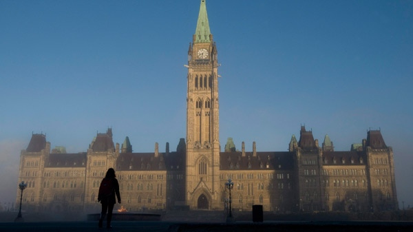 Sun illuminates the Peace Tower as a visitor makes their way onto Parliament Hill in Ottawa, Nov. 3, 2010. (Adrian Wyld / THE CANADIAN PRESS)