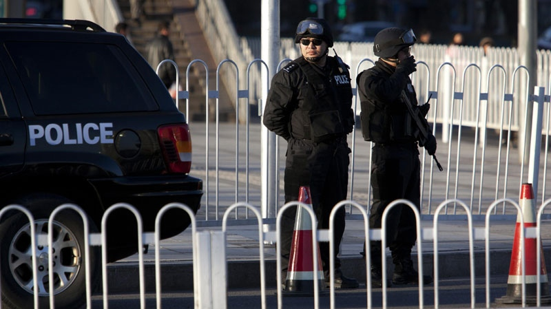 Heavily armed Chinese police officers guard an intersection near Wangfujing, one of the proposed protest spots in Beijing, China, Thursday, March 3, 2011. (AP Photo/Ng Han Guan)