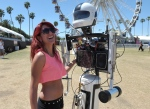 Suzie Balian interacts with 'Hotshot the Robot' at the 2nd weekend of the 2013 Coachella Valley Music and Arts Festival at the Empire Polo Club on Friday, April 19, 2013 in Indio, Calif. (Photo by John Shearer/Invision/AP)