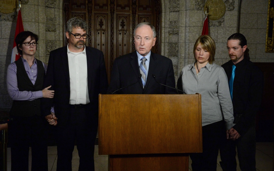 Minister of Justice Rob Nicholson speaks to reporters joined by Leah Parsons, second from right, mother of Rehtaeh Parsons and her partner Jason Barnes as well as Rehtaeh's father Glen Canning, second from left, and wife his Krista in the foyer of the House of Commons on Parliament Hill in Ottawa on Tuesday, April 23, 2013. (Sean Kilpatrick / THE CANADIAN PRESS)