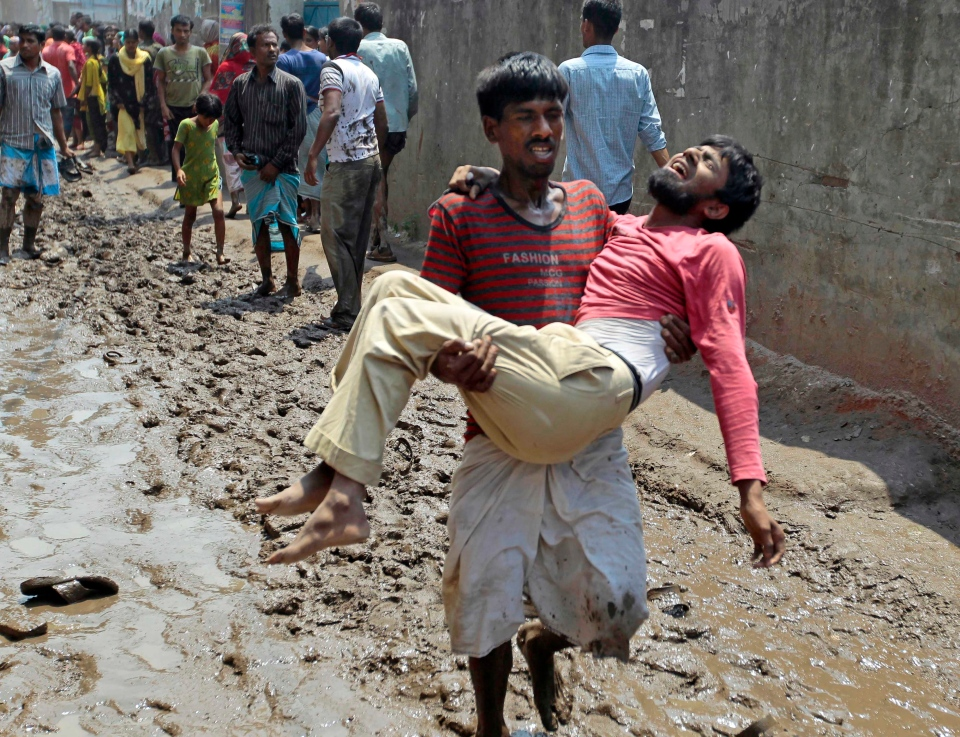A survivor reacts in pain as he is carried by a rescuer after an eight-story building housing several garment factories collapsed in Savar, near Dhaka, Bangladesh, Wednesday, April 24, 2013. (AP / A.M. Ahad)