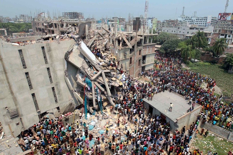 People and rescuers gather after an eight-story building housing several garment factories collapsed in Savar, near Dhaka, Bangladesh, Wednesday, April 24, 2013. (AP / A.M. Ahad)