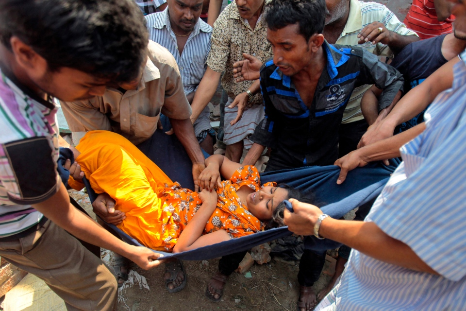 Rescuers carry a woman after an eight-story building housing several garment factories collapsed in Savar, near Dhaka, Bangladesh, Wednesday, April 24, 2013. (AP / A.M. Ahad)