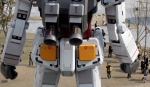 People on the ground are dwarfed by a full-size model of Japan's popular robot animation character Gundam standing in front of a new shopping mall in Tokyo's Odaiba waterfront area Tuesday, April 17, 2012. The 18-meter (60-foot)-tall Gundam greets shoppers at Diver City Tokyo Plaza which opens on Thursday. (AP Photo/Koji Sasahara)