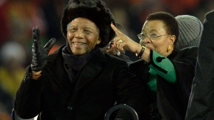 Former South African President Nelson Mandela, left, waves to spectators next to his wife Graca Machel ahead of the World Cup final soccer match between the Netherlands and Spain at Soccer City in Johannesburg, South Africa on Sunday, July 11, 2010. (AP / Martin Meissner)