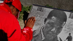 A child looks at a historical photo of Mandela, outside the cell where former South African president Nelson Mandela was locked up by the former apartheid government on Robben Island, South Africa. (AP / Schalk van Zuydam)