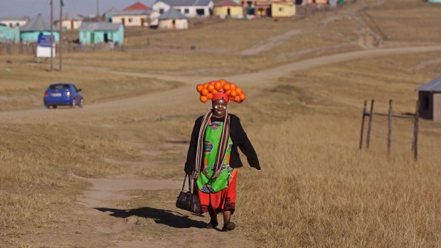 A woman carrying oranges on her head walks to a party in honour of former South African President Nelson Mandela during celebrations for Mandela's birthday in Mvezo, South Africa on Wednesday, July 18, 2012. (AP / Schalk van Zuydam)