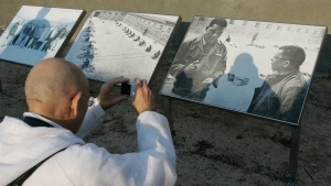 A man takes a photo of a historical photo of former South African President Nelson Mandela during his 90th birthday celebration on Robben Island, South Africa on Friday, July 18, 2008. (AP / Schalk van Zuydam)