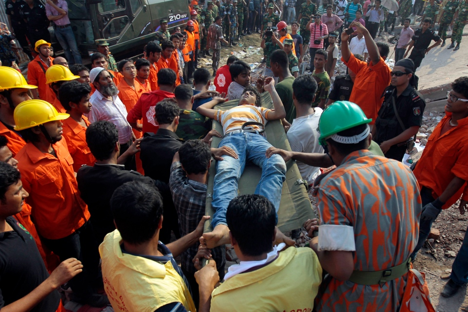 Rescuers carry a survivor out from the debris of a building that collapsed in Savar, near Dhaka, Bangladesh, Wednesday, April 24, 2013. (AP/A.M.Ahad)
