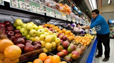 Grocery store owner Gilles Robin works on his fruits and vegetables display Tuesday Nov. 28, 2006, in the Breakeyville, a suburb of Levis, Que.