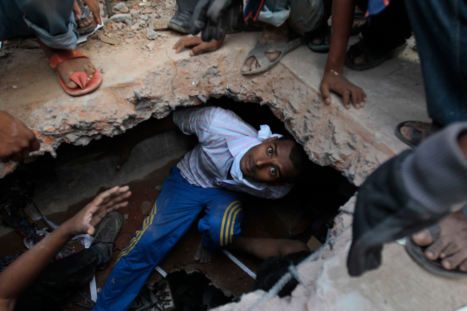 A Bangladeshi rescuer looking for survivors emerges from beneath a concrete slab of a building that collapsed in Savar, near Dhaka, Bangladesh ,Thursday, April 25, 2013. (AP / A.M.Ahad)