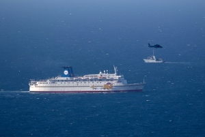 An Israeli military naval ship and an Israeli air force helicopter operate next to a cruise ship off the coast of Haifa, northern Israel, Thursday, April 25, 2013. (AP / Ariel Schalit)