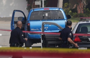 This Feb. 7, 2013 file photo law enforcement officers look over the scene of an officer involved shooting where two women were wounded after being misidentified by LAPD officers during the hunt for rogue ex-cop Christopher Dorner. (AP Photo/Chris Carlson, File)