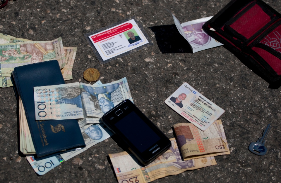 Identification cards, cash, a phone, a key and an item with a bank logo lay on the street at the site of a shooting that killed Canadian priest Richard E. Joyal. He was killed in Delmas, a district of Port-au-Prince, on Thursday, April 25, 2013. (AP / Dieu Nalio Chery)
