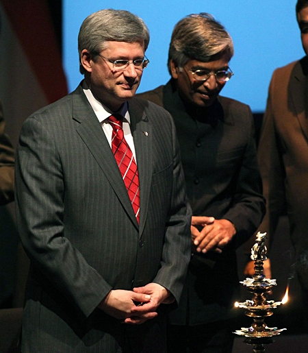 Prime Minister Stephen Harper stands next to an oil lamp at the launch of the 'Year of India in Canada 2011' at the Museum of Civilization in Gatineau, Que., on Friday, March 4, 2011. (Patrick Doyle / THE CANADIAN PRESS)