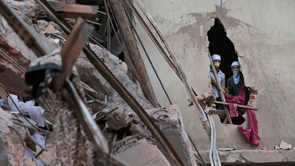 Bangladeshi rescue workers watch from a damaged section of a wall at the site of a building that collapsed Wednesday in Savar, near Dhaka, Bangladesh, Thursday, April 25, 2013. (AP / Kevin Frayer)