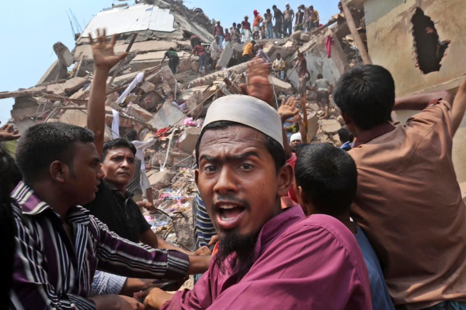 Bangladeshi rescue workers work at the site of a building that collapsed Wednesday in Savar, near Dhaka, Bangladesh, Friday, April 26, 2013. (AP Photo/Kevin Frayer)