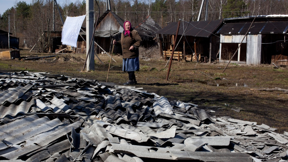 An elderly woman looks at roof debris at a site of a fire of a psychiatric hospital Friday, April 26, 2013. (AP / Pavel Sergeyev)