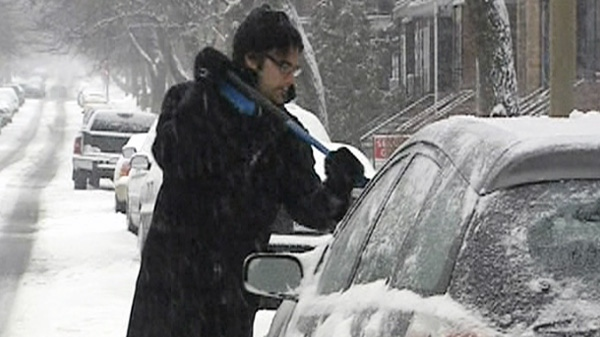 A motorist cleans snow and ice off of his car in Montreal on Sunday, March 6, 2011.