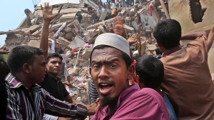 Bangladeshi rescue workers work at the site of a building that collapsed Wednesday in Savar, near Dhaka, Bangladesh, Friday, April 26, 2013. (AP / Kevin Frayer)