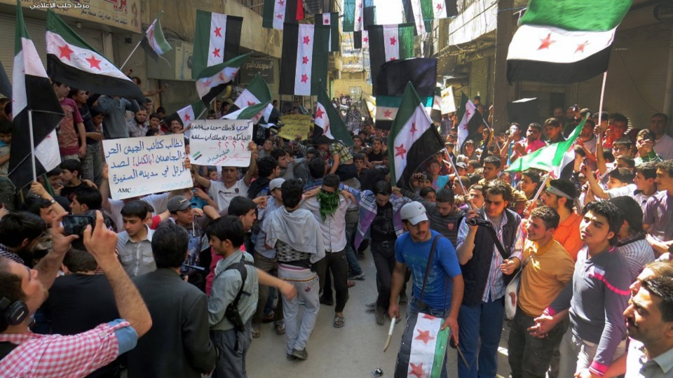 This citizen journalism image provided by Aleppo Media Center AMC which has been authenticated based on its contents and other AP reporting, shows anti Syrian regime protesters holding banners and waving the Syrian revolutionary flags during a demonstration, in Aleppo, Syria, Friday, April 26, 2013. (AP / Aleppo Media Center AMC)