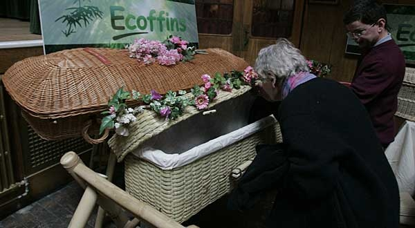 A woman looks into a coffin made of willow at a 'green funeral' exhibition in London, Saturday April 19, 2008. (AP Photo/Alastair Grant)