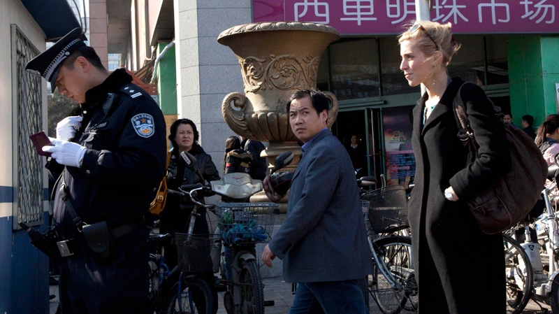 A Chinese policeman checks the identity of a foreign journalist, right, near the Xidan shopping district, one of two sites designated on an Internet call for protest in Beijing Sunday, March 6, 2011. (AP Photo)