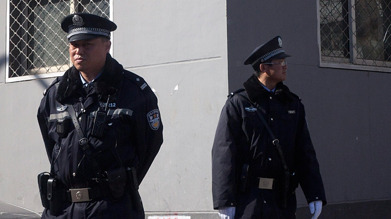 Chinese police officers stand on duty near the Xidan shopping district, one of two sites designated on an Internet call for protest, in Beijing Sunday, March 6, 2011. (AP)