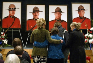 Residents of Mayerthorpe, Alta., embrace during a candlelight memorial service Friday, March 3, 2006. (CP / Jeff McIntosh)