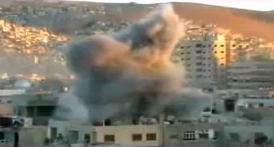An explosion is seen during heavy fighting between rebels and Syrian government forces in the Barzeh district of Damascus, Syria, Friday, April 26, 2013. (Ugarit via AP video)