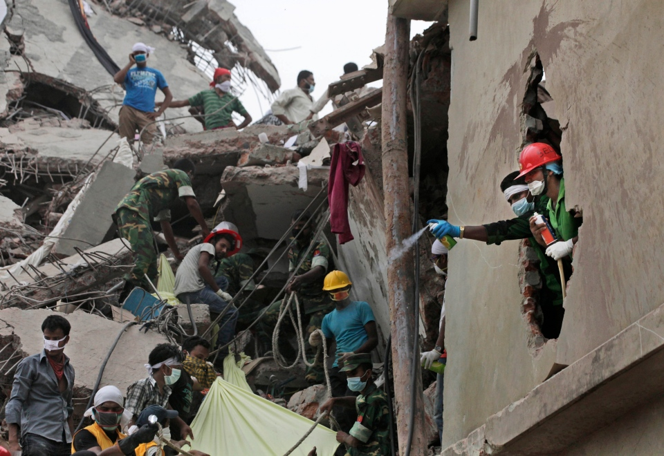 Bangladeshi spray deodorant to mask the smell of bodies amid the rubble of a building that collapsed Wednesday in Savar, near Dhaka, Bangladesh, Friday, April 26, 2013. (AP / A.M. Ahad)