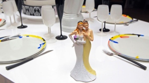 Plastic figurines of two females displayed on a table, at the Gay marriage fair, in Paris, Saturday, April 27, 2013. Lesbian and gay cake toppers, his-and-his wedding bands, flower-themed tuxedo bow ties: Marketing whizzes have held France's first gay-marriage fair — four days after parliament legalized same-sex wedlock. Wedding planners, photographers and high-end tailors pitched their services at the Paris fair Saturday. Police stood guard outside — a precautionary measure after recent bouts of anti-gay violence by foes of same-sex marriage. The legislation sparked huge protests across France. (AP Photo/Jacques Brinon)