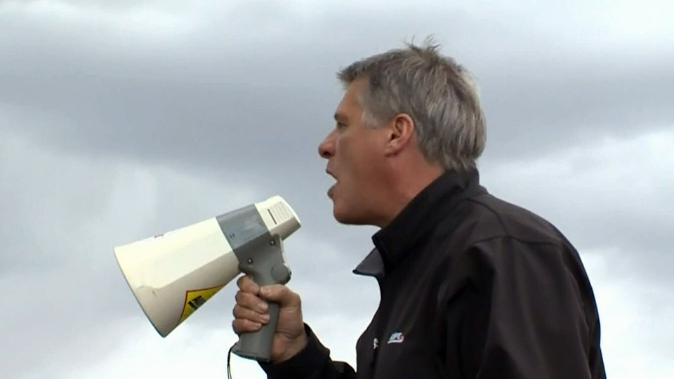 Guy Smith, president of the Alberta Union of Provincial Employees, speaks to protesters with a megaphone outside the Remand Centre in Fort Saskatchewan.