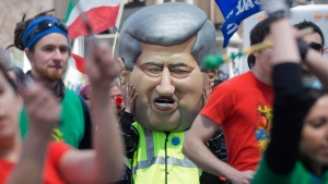 A protester opposing employment insurance reform wears a puppet head of prime minister Stephen Harper during a demonstration in Montreal, Saturday, April 27, 2013. (Graham Hughes / THE CANADIAN PRESS)