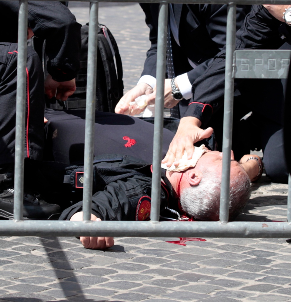 A wounded Carabinieri paramilitary police officer lies on the ground after being shot outside the Chigi Premier's office, in Rome, Sunday, April 28, 2013. (AP / Gregorio Borgia)