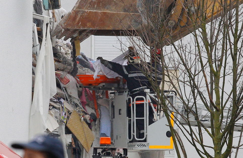 French firemen carry the body of an unidentified victim from a building hit by an explosion that caused the collapse of its inside floors, in Reims, eastern France, Sunday, April 28, 2013. (AP / Jacques Brinon)