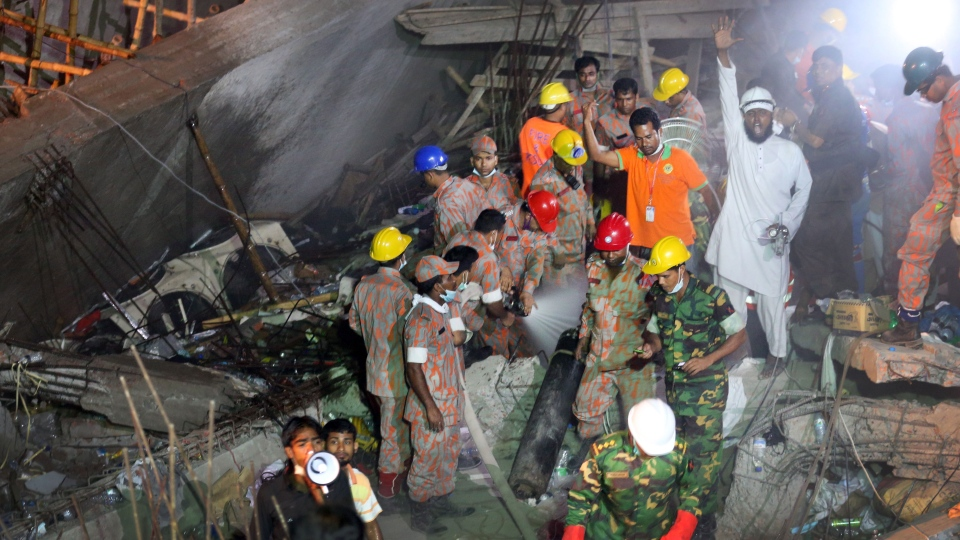 Rescue workers call for help while fire fighters, center, hose out a fire which broke out in a garment factory building which collapsed Wednesday in Savar, near Dhaka, Bangladesh, Sunday April 28, 2013. (AP / Wong Maye-E)