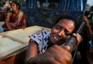 A Bangladeshi woman weeps as she sits next to the coffin of a relative who died in a building that collapsed Wednesday in Savar, near Dhaka, Bangladesh, Sunday, April 28, 2013. (AP / Kevin Frayer)