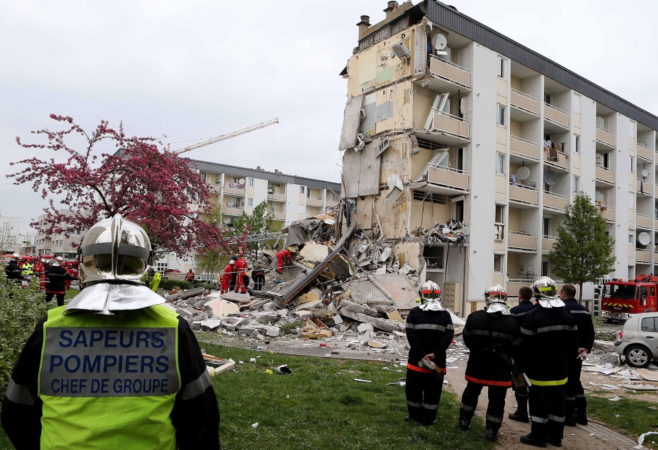 French firemen attend the scene of a building hit by an explosion that caused the collapse of its inside floors, in Reims, eastern France, Sunday, April 28, 2013. (AP / Jacques Brinon)