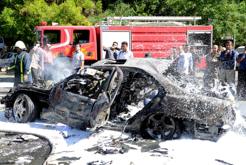 Syrian fire fighters are seen extinguishing burning cars after a car bomb exploded in the capital's western neighborhood of Mazzeh, in Damascus, Syria, Monday, April. 29, 2013. (SANA)