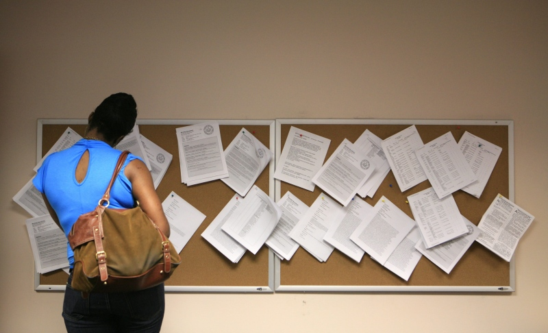 Examining a help wanted bulletin board. (AP / Mark Lennihan)