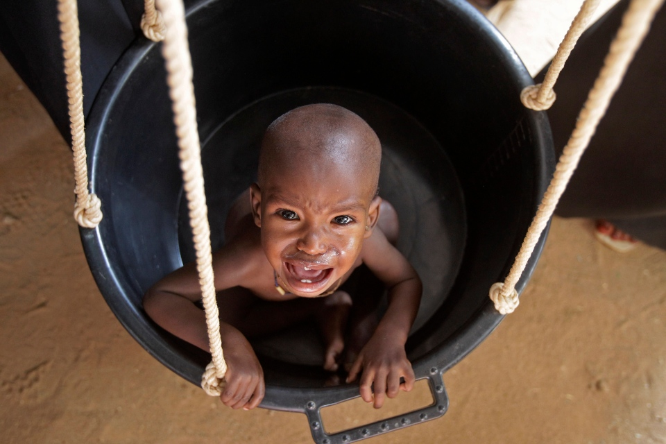 An unidentified child reacts as he is weighed at a field hospital of Medecins Sans Frontieres in the town of Dadaab, Kenya, in this 2011 file photo. Officials in East Africa say a report to be released this week by two U.S. government-funded famine and food agencies gives the highest death toll yet from Somalia's 2011 famine, estimating that 260,000 people died - more than double previous estimates. (AP Photo/Schalk van Zuydam)