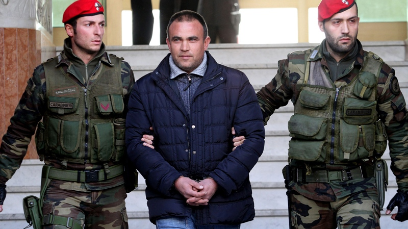 A man identified as Francesco Maisano, centre, is escorted by Italian Carabinieri paramilitary police officers soon after after his arrest in Reggio Calabria, southern Italy, on Tuesday, March 8, 2011. (AP / Adriana Sapone)