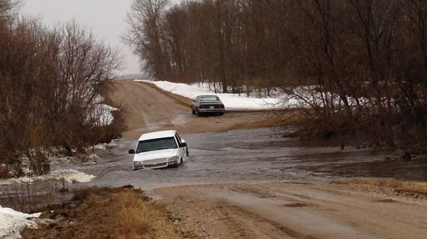 The RCMP rescued a man and his daughter, 12, after their vehicle became trapped on a flooded road in central Manitoba. (CTV Winnipeg)