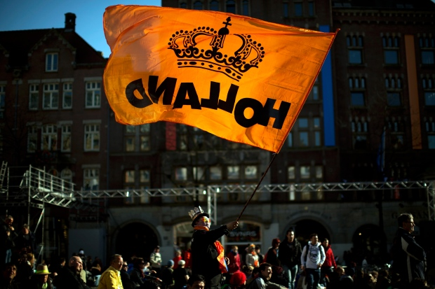 A man waves a flag with the color of the House of Orange of the Dutch Royal Family in Dam square in downtown Amsterdam, Netherlands, Monday, April 29, 2013. (AP / Emilio Morenatti)