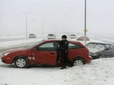 A motorists who spun off the highway during a snowstorm surveys the damage in Edmonton on Monday, April 21, 2008.
