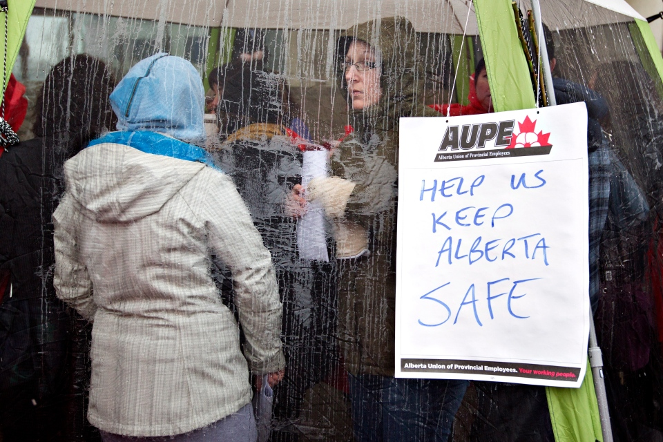 Alberta sheriffs stay dry in a tent while taking part in a strike as they joined correction guards, setting up a picket line outside the Edmonton courthouse in Edmonton, Alberta on Monday, April 29, 2013. (Jason Franson / THE CANADIAN PRESS)